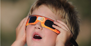 Young boy looking at the solar eclipse with special glasses